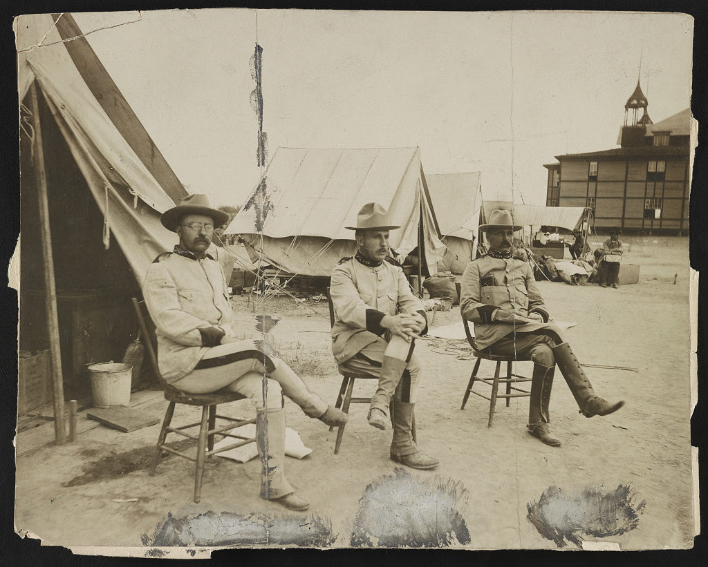Photograph showing Theodore Roosevelt, Leonard Wood, and Alexander O. Brodie sitting in front of camp tents in San Antonio, Texas.